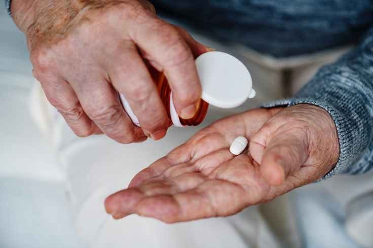 person holding white medication tablet